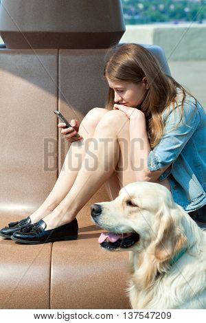 Portrait of a young girl with a smartphone in the hands on a park bench, next to her dog outdoors. The owner is sitting next to his dog breed golden retriever on a background of summer city. Human friendship and dogs. Joint pastime.