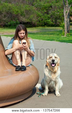Portrait of a young girl with a smartphone in the hands on a park bench, next to her dog outdoors. The owner is sitting next to his dog breed golden retriever on a background of summer city. Human friendship and dogs. Joint pastime..