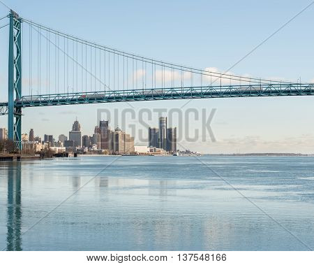 DETROIT MI/USA - JANUARY 29 2016: Ambassador Bridge reflection in an icy Detroit River, from Riverside Park. Visible: GM Renaissance Center and Cobo Center.