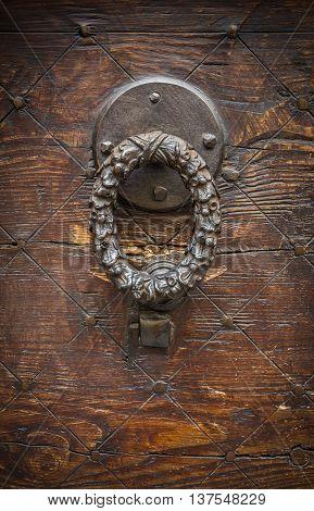 Vintage image of ancient door knocker on a wooden door