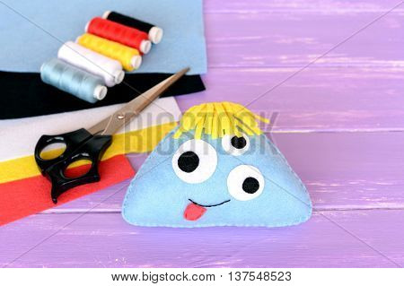 Hand made felt monster toy. Soft stuffed toy, colored thread, felt sheets, scissors on lilac wooden table. Happy Halloween crafts idea for kids. Wool monster sewing pattern