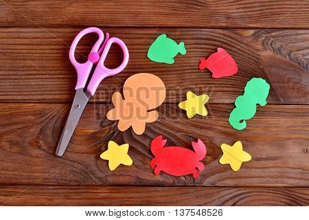 Marine animals cut from colored paper - octopus, fish, starfish, seahorse, crab. Kids sea animals arts and crafts. Scissors on wooden background. Activity idea place for preschool children