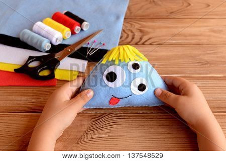 Child holds a felt monster in his hands. Funny soft toy for kids. Sewing craft supplies and tools on a wooden table. Felt Halloween ornament. Easy sewing fabric monster doll