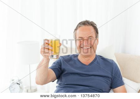 Retired man looking at the camera while he is drinking oranje juice at home
