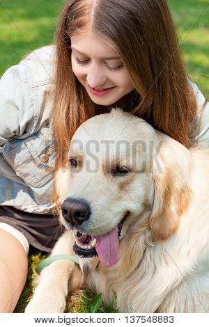 Up portrait of a young girl and her dog outdoors on a summer day. The owner is sitting next to his dog breed golden retriever on a background of summer park. Human friendship and dogs. Joint pastime.