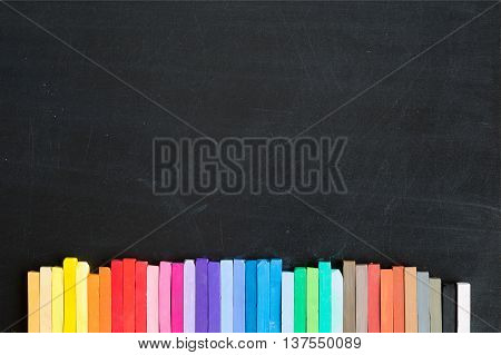 Colorful chalks lined up on blackboard background banner