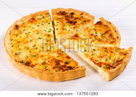 onion cheese quiche or pie sprinkled with parsley and spring onion cut into portion on white worktop view from above