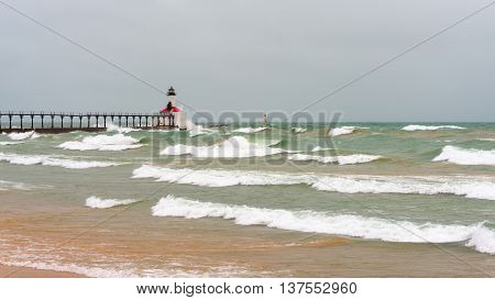 Lake Michigan waves crash against the East Pierhead Lighthouse and catwalk, in Michigan City, Indiana.