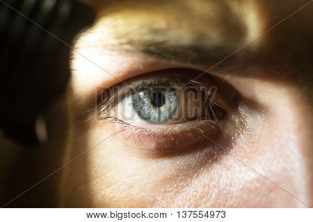young male with hairy eyebrow on serious face lighting on eye with flashlight in studio closeup