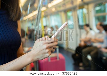 Woman using mobile phone inside train compartment