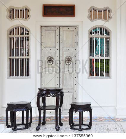Chinese style of table and stools in the front of the antique house.