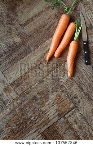 vertical top view of three carrots next to a knife on wooden background