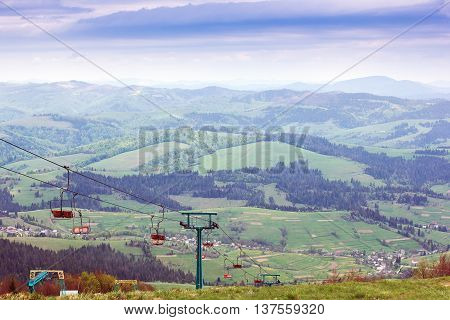 landscape consisting of the elevator in mountains on the foreground and Carpathians mountains with green meadows and fir-trees and sky on the background