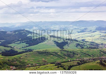 landscape consisting of a Carpathians mountains with green trees and grassy valley with little house and blue sky with white clouds