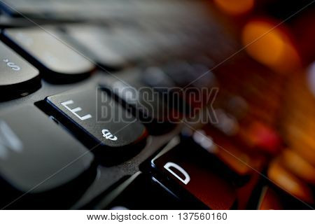 Detail of a brand new modern black laptop keyboard with the focus on the key with Euro currency(€) symbol