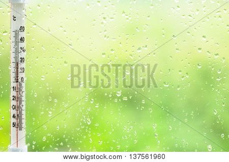 Rain Drops On Window Glass And Thermometer