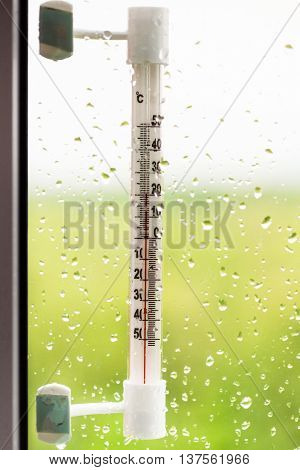 Thermometer And Rain Drops On Window Glass