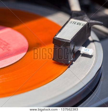 tonearm of turntable on orange vinyl record close up