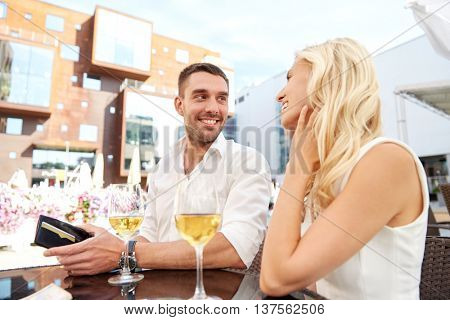 date, people, payment and finances concept - happy couple with wallet and wine glasses paying bill at restaurant