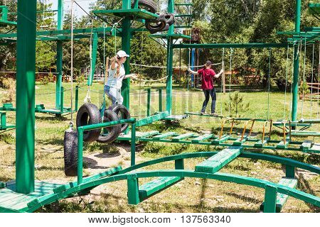 two girls pass an outdoor obstacle course in sunny summer day
