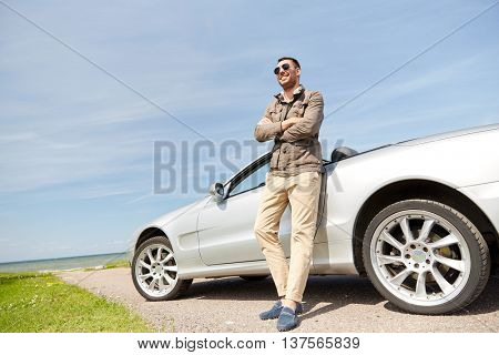 road trip, travel, transport, leisure and people concept - happy man near cabriolet car outdoors