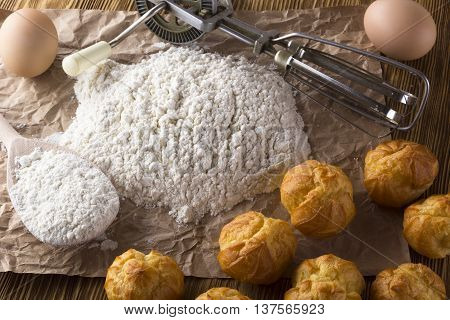 Tasty eclairs, eggs, flour and handle mixer on wooden background.