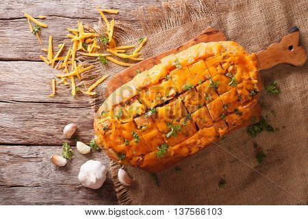 Loaf Of Bread Baked With Cheddar Cheese, Garlic And Herbs Closeup. Horizontal Top View
