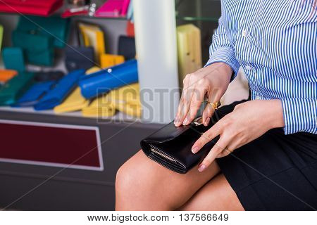 Shop accessories. Business buyer opens wallet beautiful female hand closeup. behind Showcases with accessories
