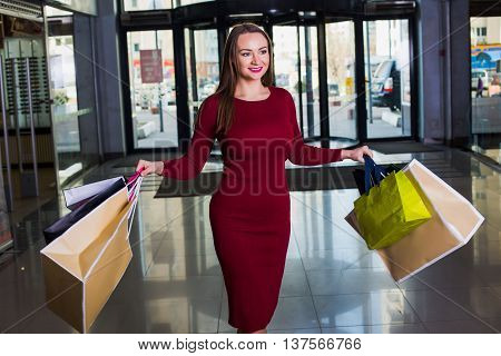 Portrait of beautiful happy welldressed woman with shopping bags. Shopping center. Successful  day.