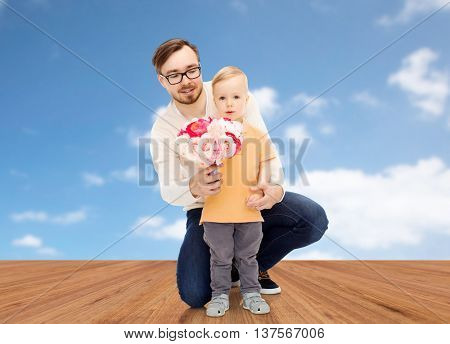 family, childhood, fatherhood, holidays and people concept - happy father and and little son with bunch of flowers over blue sky and wooden floor background