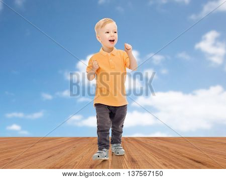 childhood, fashion, emotion, expression and people concept - happy little boy in casual clothes having fun over blue sky and wooden floor background