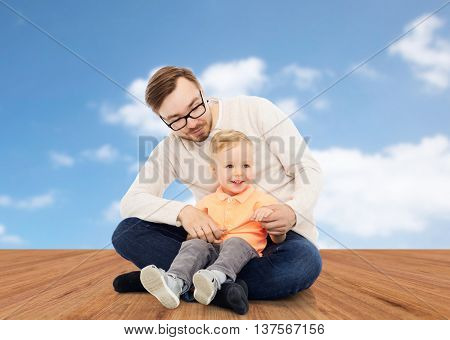 family, childhood, fatherhood, leisure and people concept - happy father and and little son over blue sky and wooden floor background