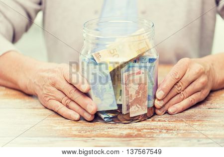savings, money, annuity insurance, retirement and people concept - close up of senior woman hands with money in glass jar