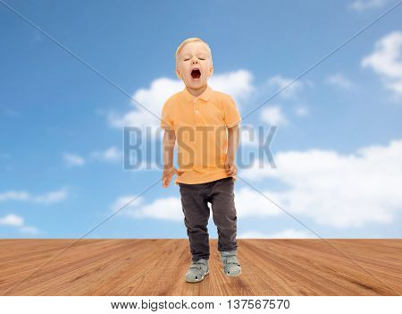 childhood, emotion, expression and people concept - happy little boy in casual clothes shouting, crying or sneezing over blue sky and wooden floor background