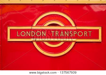 WEYBRIDGE SURREY UK - AUGUST 9 2015: A vintage Red London Transport badge on a vintage London bus at the London Bus Museum at Brookland Motor Museum in August 2015.