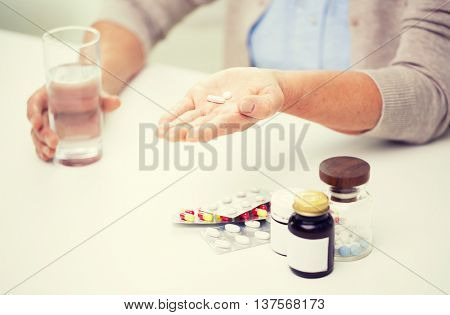 age, medicine, health care and people concept - close up of senior woman with pills and glass of water at home