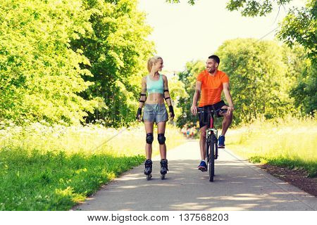 fitness, sport, summer, people and healthy lifestyle concept - happy couple with roller skates and bicycle riding and talking outdoors at summer