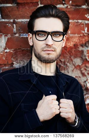 Handsome man in black jacket and spectacles posing outdoor by a brick wall. Men's beauty, fashion. Business style.