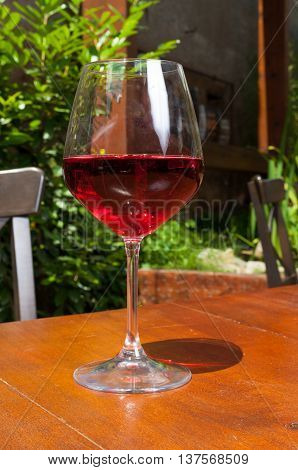 Glass of rose wine on wooden terrace table in sunny day outdoor