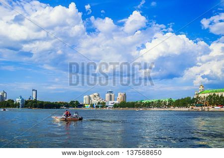 YEKATERINBURG RUSSIA - AUGUST 17 2013. Panorama of Ykaterinburg - water area of Iset river with modern buildings along the embankment and motorboat floating on the river. Urban summer landscape