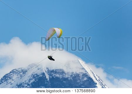 Paragliding in the mountains with blue sky and cloud