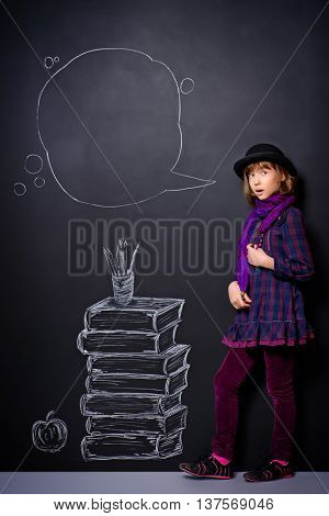 Educational concept. Teen girl standing by the background of the school board with drawn stack of books.