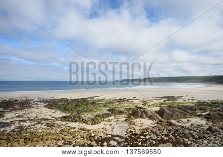 Empty Beach with stones in foreground and blue and cloudy skies