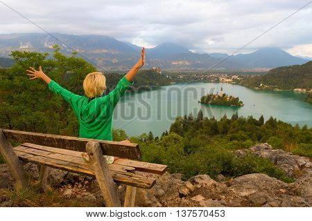 Relaxed female traveler, arms rised, enjoying beautiful panoramic view of Julian Alps, Lake Bled with St. Marys Church of the Assumption on the small island, Bled, Slovenia, Europe.