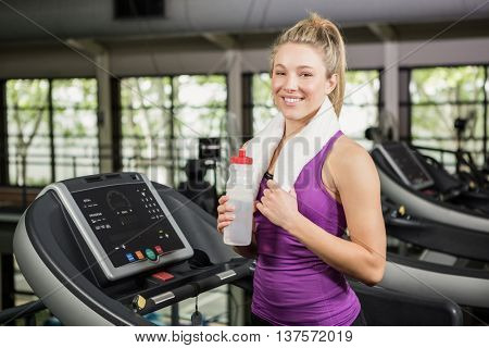 Woman on treadmill holding water bottle while exercising in gym