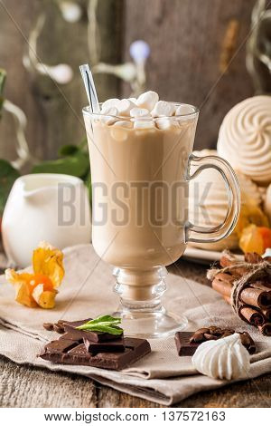 Hot latte with marshmallows in a glass cup on the wooden background.  X-mas concept.