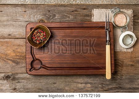 Cutting board, seasonings and meat fork on  wooden background, top view