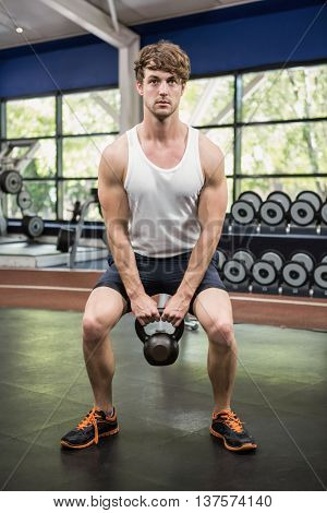 Determined man lifting kettle bells at gym