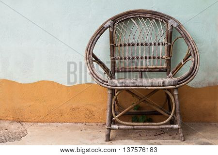 Wicker armchair with old wall background, retro style