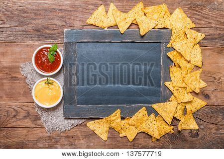 Mexican nacho with sauces and chalk board on wooden background, top view, copy space